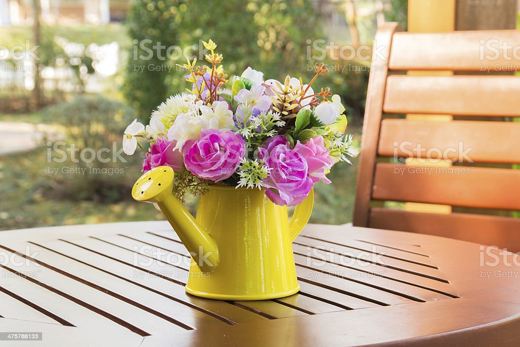 Bouquet of flowers in watering can on wooden table stock photo