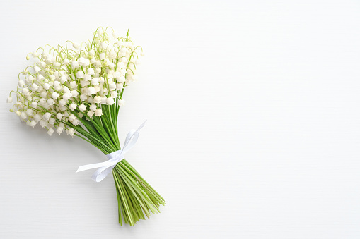 Bouquet of flowers lily of the valley on white background. Flat lay, top view with copy space. Greeting card mockup for Mother's Day, Woman's Day