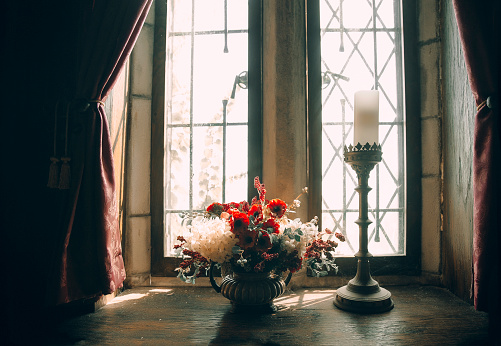 bouquet of flowers on the window of an old house