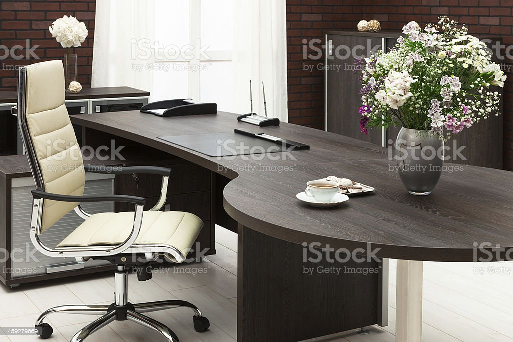 Bouquet of flowers sitting on a large desk in an office stock photo