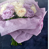 Bouquet of fresh amazing white and purple roses in craft paper on dark background for postcard, cover, banner. Beautiful flowers as gift for Mother's, Valentine's Day, Birthday or Wedding. Copy space