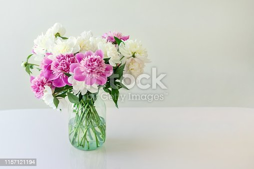 Bouquet of fresh big pink, white and cream peonies in simple glass jar on glance table indoor. Vase with beautiful tender spring flowers on glass table.