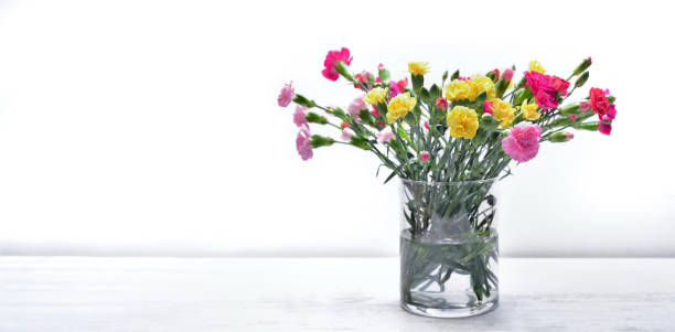 ramo de flores frescas clavel colorido en un frasco de vidrio en una mesa - foto de stock