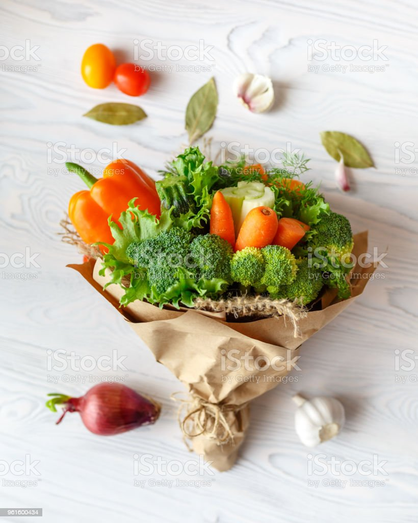 Bouquet of fresh vegetables lies on a white wooden table. Nearby is a red onion, tomatoes, garlic, bay leaf. View from above stock photo