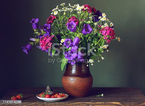 bouquet of garden flowers, butterfly and strawberry on green background.