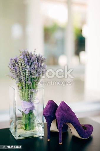 A bouquet of lavender in a glass vase and purple high-heeled women's shoes. High quality photo