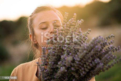 Woman has closed eyes and holds a bouquet of lavender