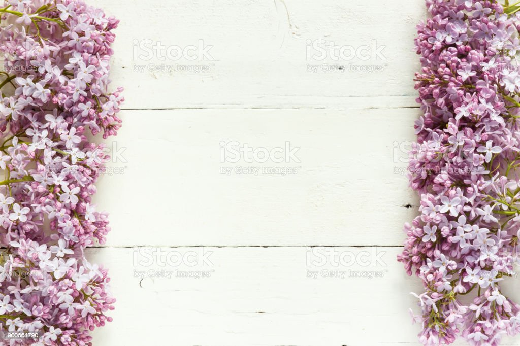 Bouquet of lilac flowers on white wooden background. stock photo
