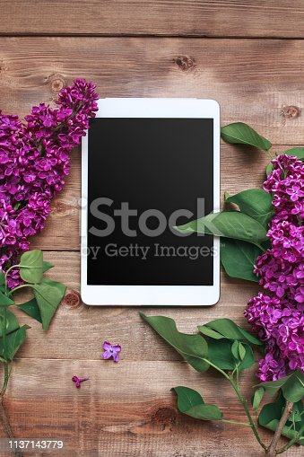 Bouquet of lilac flowers on wooden planks with tablet. Top view and flat lay