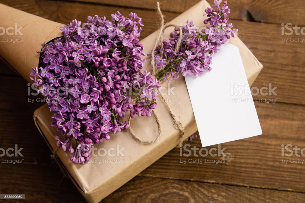 Bouquet of lilacs on a wooden table with a gift box stock photo