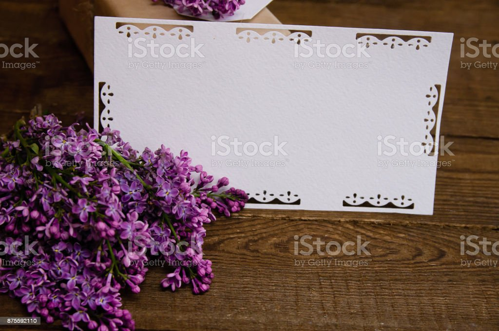 Bouquet of lilacs on a wooden table with an inscription card stock photo
