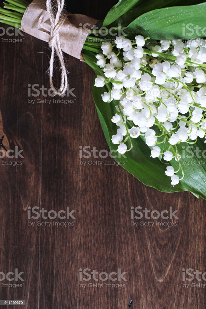 Bouquet of young lilies of the valley on a wooden table