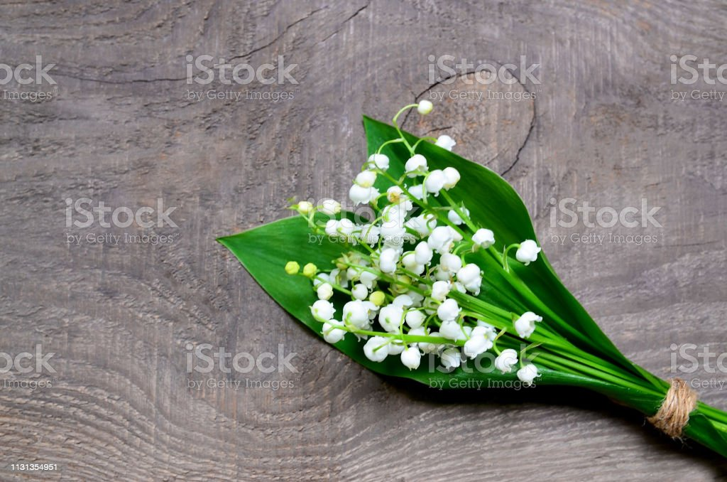Bouquet of lilies of the valley on old wooden background.Lily of the...