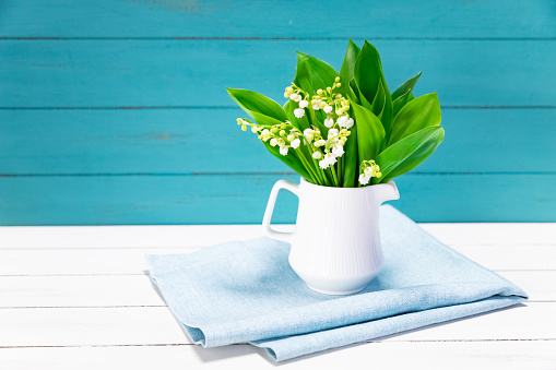 Bouquet of Lilies of the Valley isolated on wooden background
