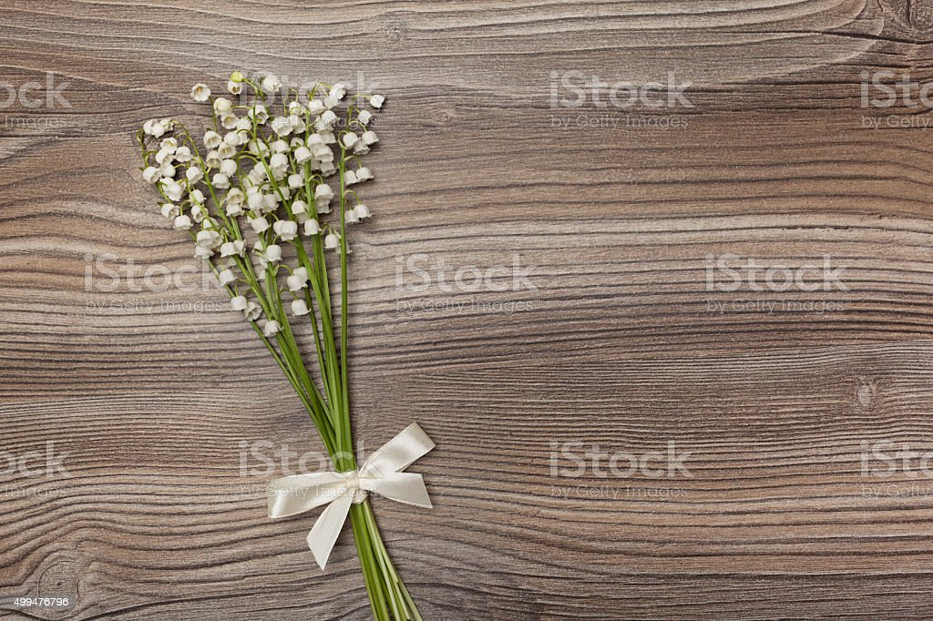 Bouquet of lily of the valley lies on an oak background. The...