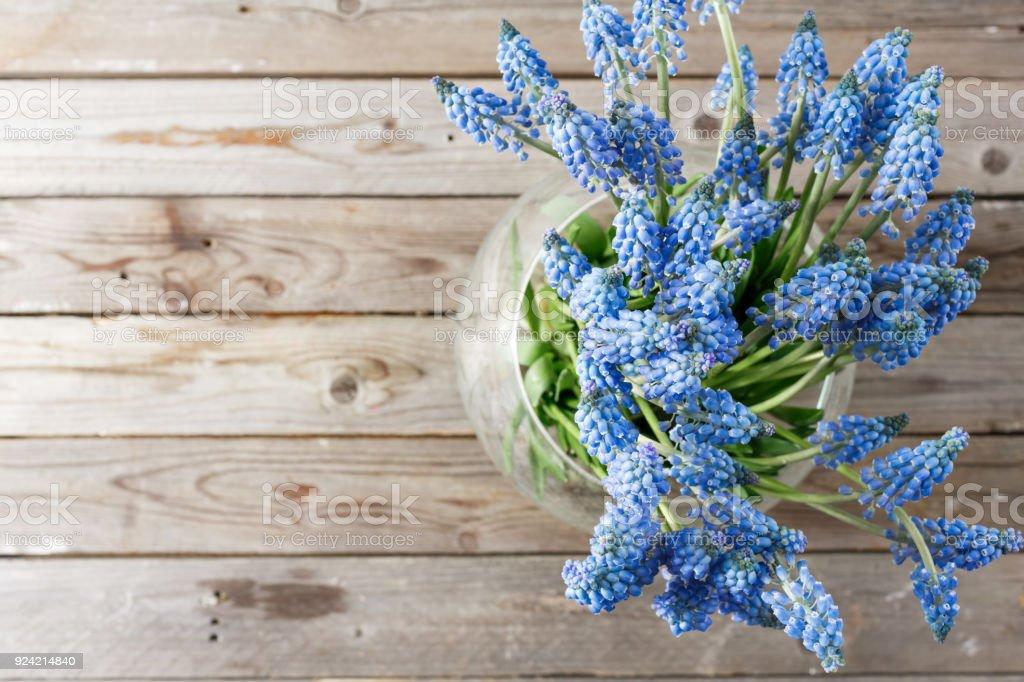 Bouquet von Muscari Blumen in Glasvase. Hölzerne rustikalen Hintergrund. – Foto