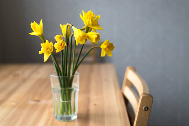 Bouquet of narcissus in glass on wooden table