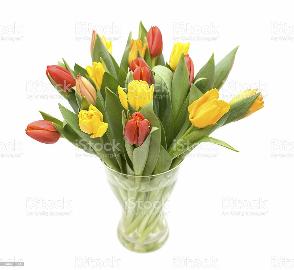 Bouquet of orange and yellow tulips in a clear glass vase stock photo