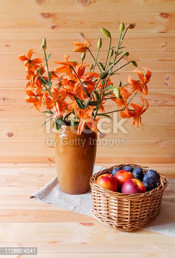 Bouquet of orange lilies in clay vase and fruits in wicker basket on wooden background. Selective focus.