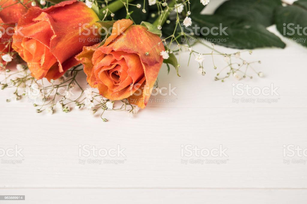 A bouquet of orange roses and gypsophila on wooden table. Copy space - Royalty-free Anniversary Stock Photo
