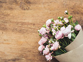 istock Bouquet of pink roses in craft paper on wooden background. Top view, flat lay. Florist workplace. Rustic still life banner with copy space. 1272976199
