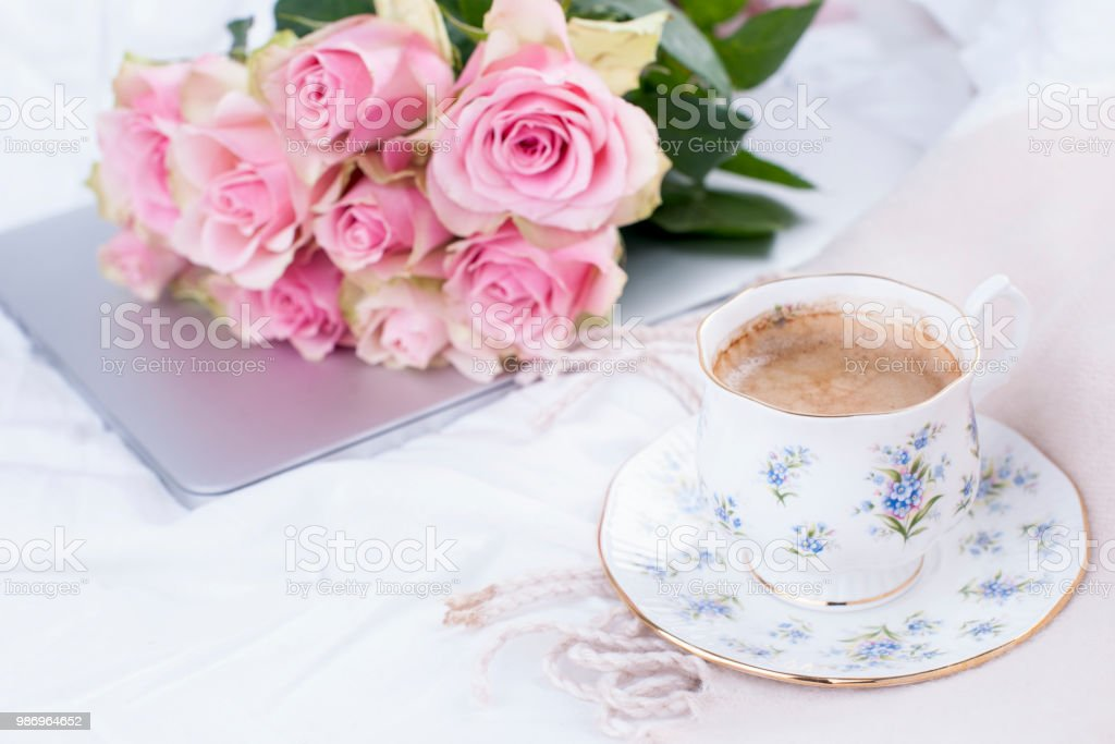 A bouquet of pink roses in the bed, a computer and a morning aromatic...