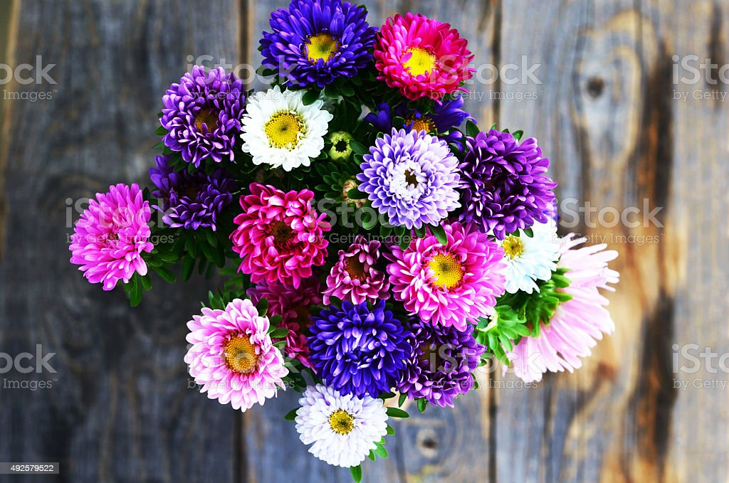 Bouquet of pink, violet and white aster over wooden background stock photo