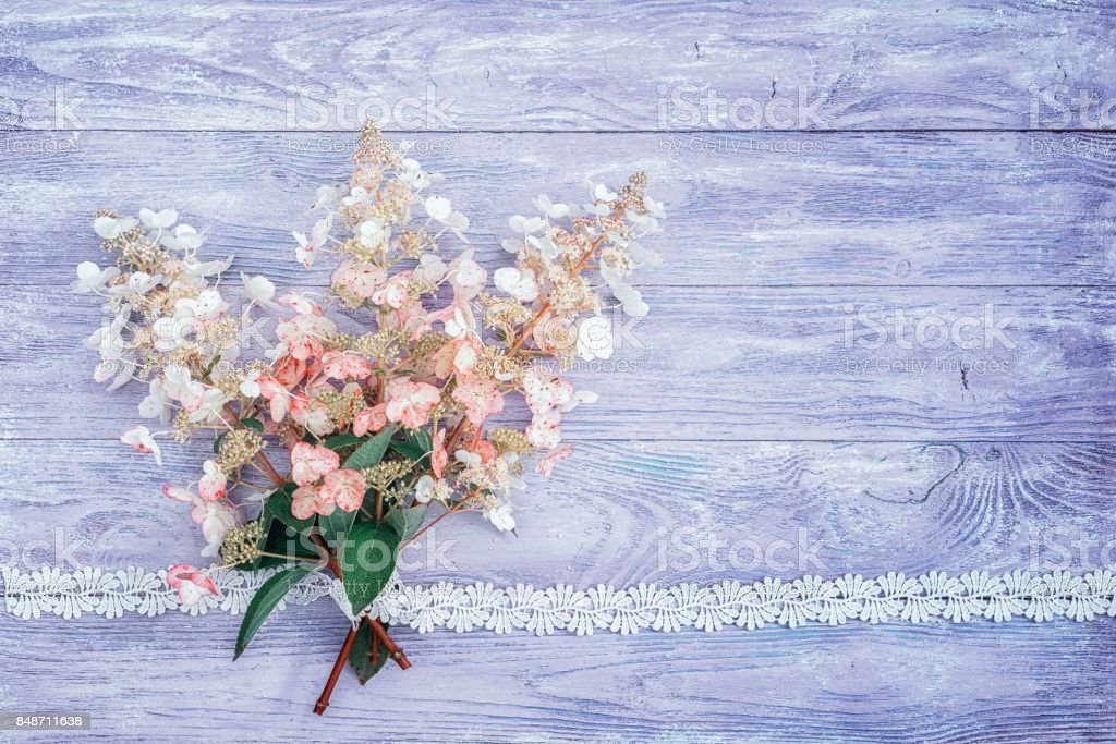 bouquet of pink-white hydrangeas on a wooden table, tied with a lace ribbon and lace as a frame, top view with copy space for your text. suitable as a wedding or birthday invitation card background. stock photo