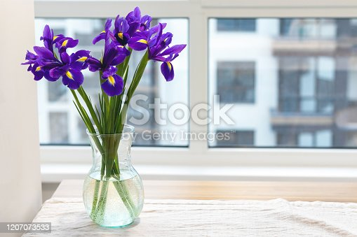 istock Bouquet of purple irises in a clear glass vase on a linen tablecloth on a wooden table by the window in a modern bright kitchen against a blurred background 1207073533