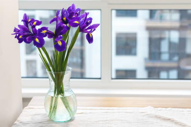 Bouquet d'iris violets dans un vase en verre clair sur une nappe en lin sur une table en bois près de la fenêtre dans une cuisine lumineuse moderne sur un fond brouillé - Photo