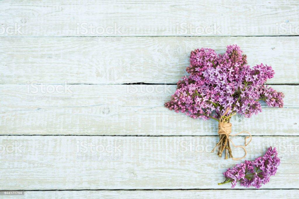 Flores Lilas Con Rosas Sobre Fondo: Ramo De Flores Lilas Púrpura Sobre Un Fondo De Madera