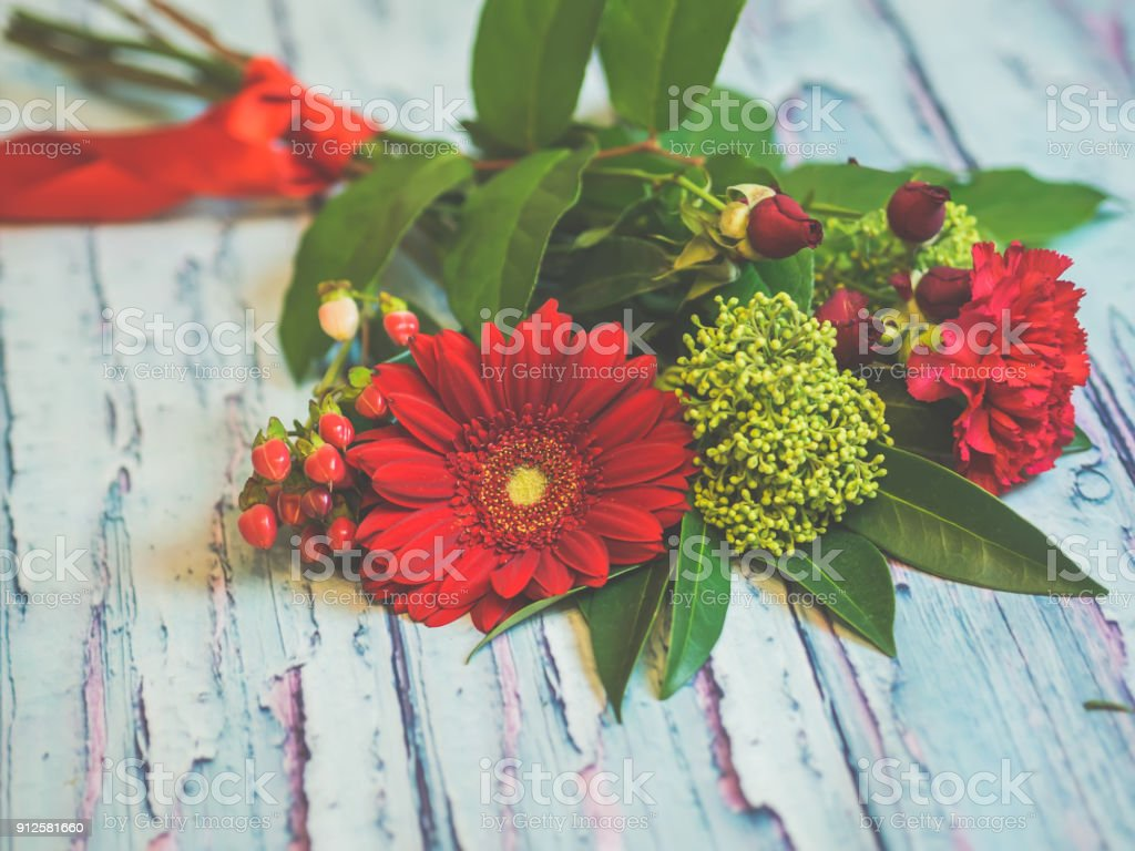 A Bouquet Of Red And Green Flowers Lying On A Wooden Table Against
