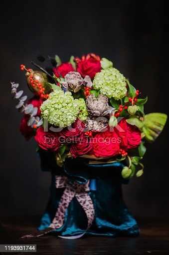 Beautiful bouquet of red roses, hydrangea and dried flowers on a dark background