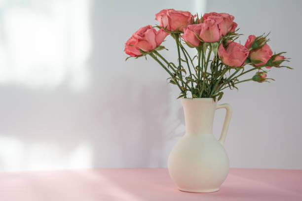 Bouquet of red roses in vase on a pink table on beige background with soft sunlight. Copy space Simple bouquet of red roses in vase on a pink table on light background. sentimentality stock pictures, royalty-free photos & images