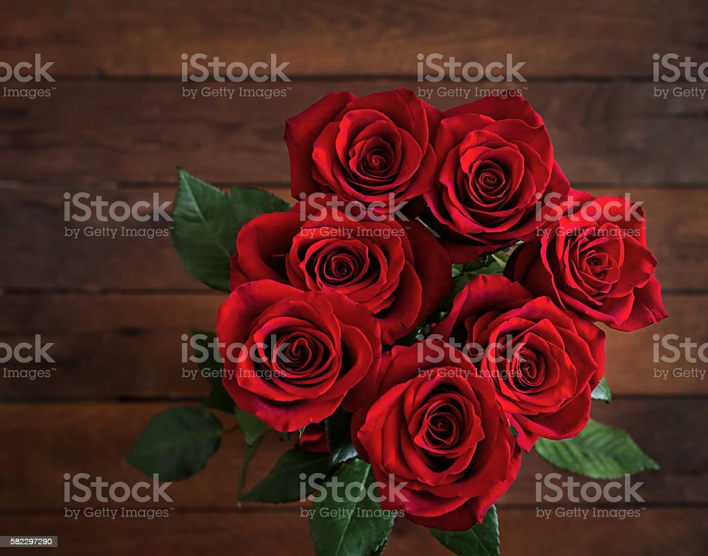 Bouquet of red roses on a dark wooden background. stock photo