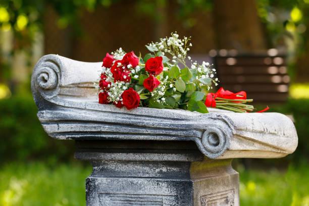 boeket van rode rozen op een grafsteen op de begraafplaats. - graf stockfoto's en -beelden