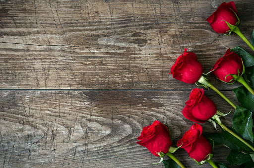 Bouquet of red roses on old wooden background. Top view