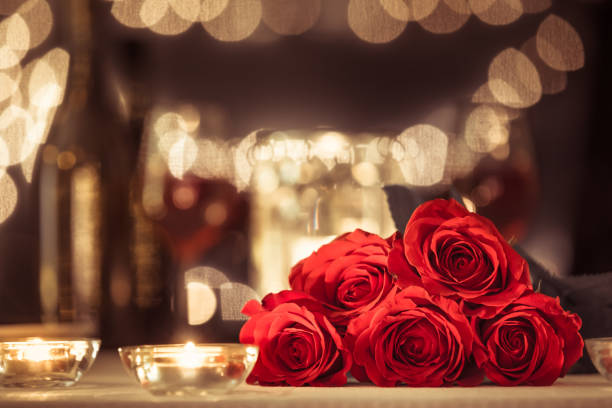 Bouquet of red roses Bouquet of red roses in a romantic restaurant setting. table for two stock pictures, royalty-free photos & images