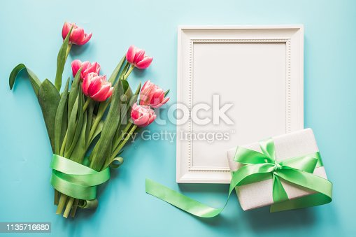 659293084istockphoto Bouquet of red tulip and gift box on blue. Top view with copy space. 1135716680