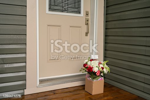 A bouquet of red white flowers in a carton box on a porch doorstep of a house. Surprise contactless delivery of flowers for woman. Delivery of goods home during quarantine. A pleasant unexpected gift.