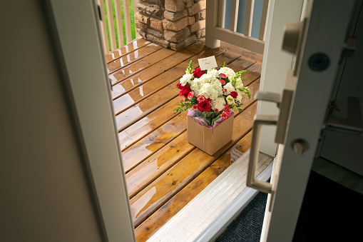 A bouquet of flowers in a carton box on a porch of a house through open door. Surprise contactless delivery of flowers for woman. Delivery of goods home during quarantine. A pleasant unexpected gift.