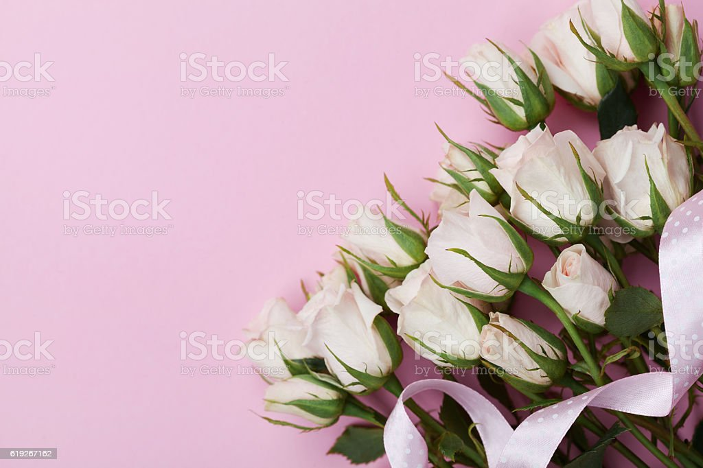 Bouquet of rose flowers on pink background. Flat lay styling. stock photo
