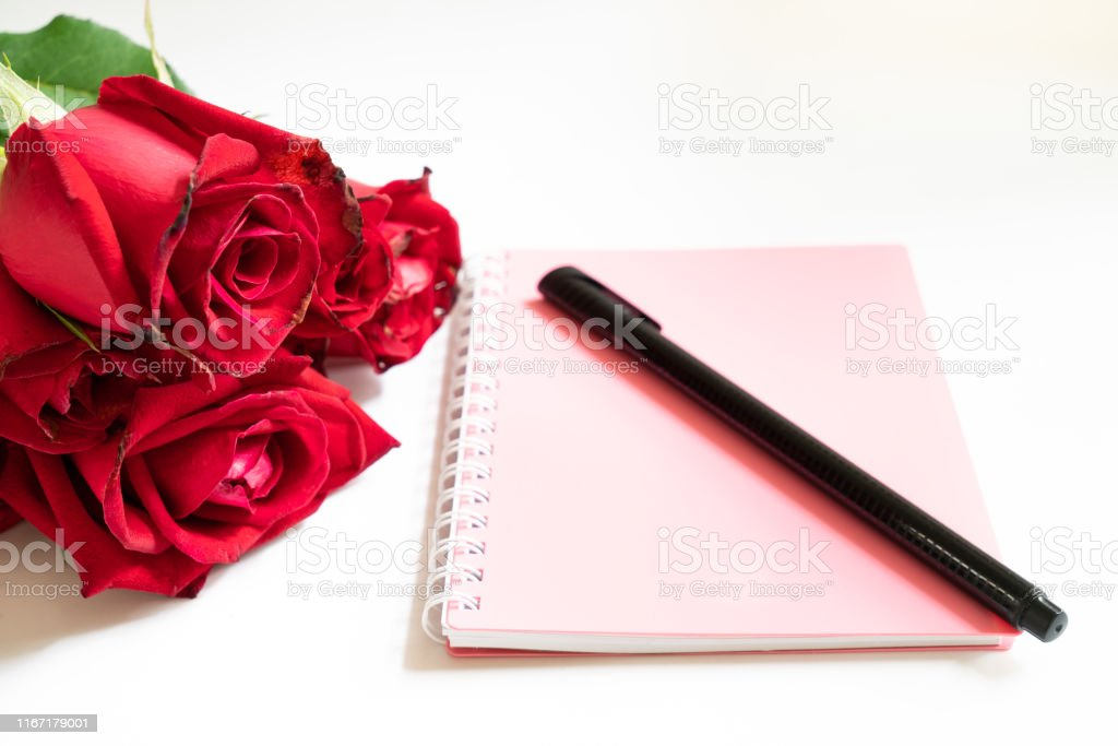 Bouquet of roses and a note book and a pen isolated on white...