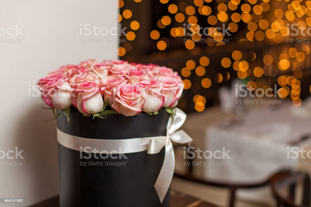 A bouquet of roses in a box against the background of blurred lights royalty-free stock photo