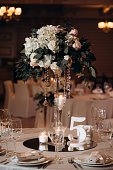 bouquet of roses in a glass vase on a festive table. Festive table in the restaurant hall with a bouquet of white and pink roses. Served holiday table in restaurant