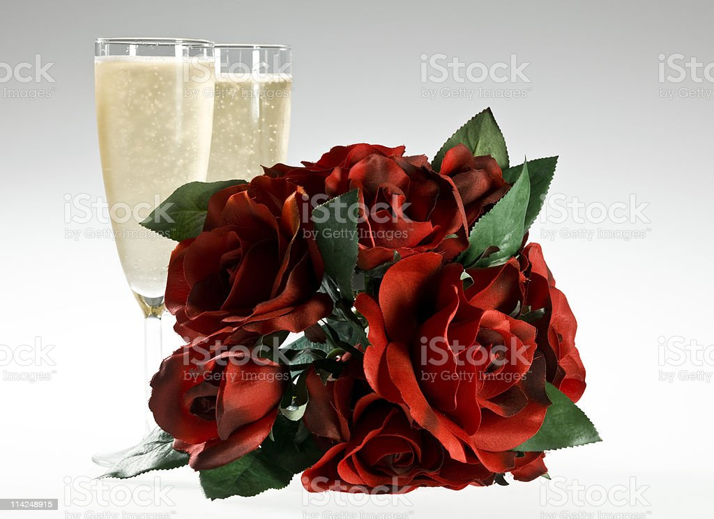Bouquet of roses in front of two filled champagne glasses royalty-free stock photo