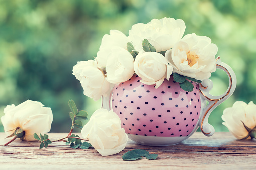 Bouquet of roses in tea kettle.