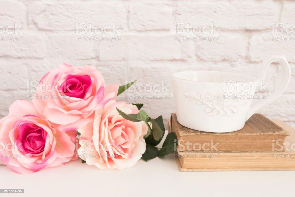 Bouquet de roses sur un bureau blanc une grande tasse de café plus