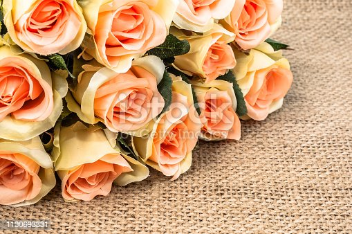 680461500istockphoto Bouquet of roses on rustic background. Mothers day card. 1130693331