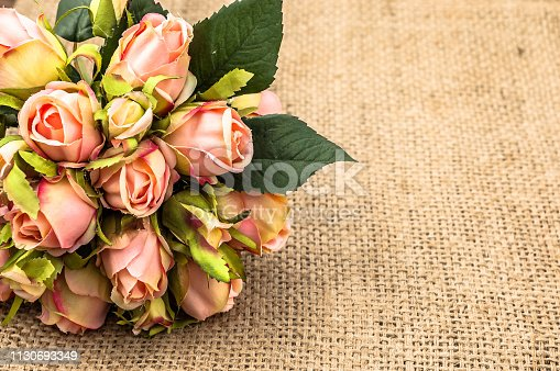 680461500istockphoto Bouquet of roses on rustic background. Mothers day card. 1130693349